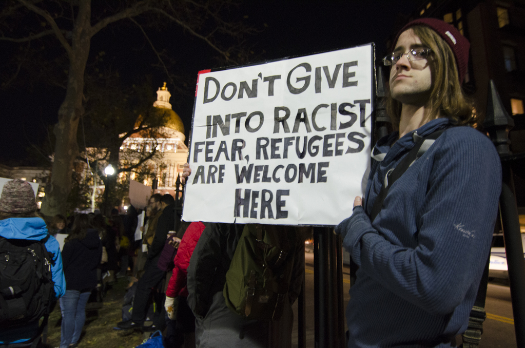 """Protester holds placard reading """"don't give in to racist fear, refugees are welcome here"""""""