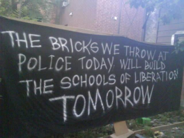 """A black banner reading: """"The bricks we throw at police today will be the schools of revolution tomorrow"""""""