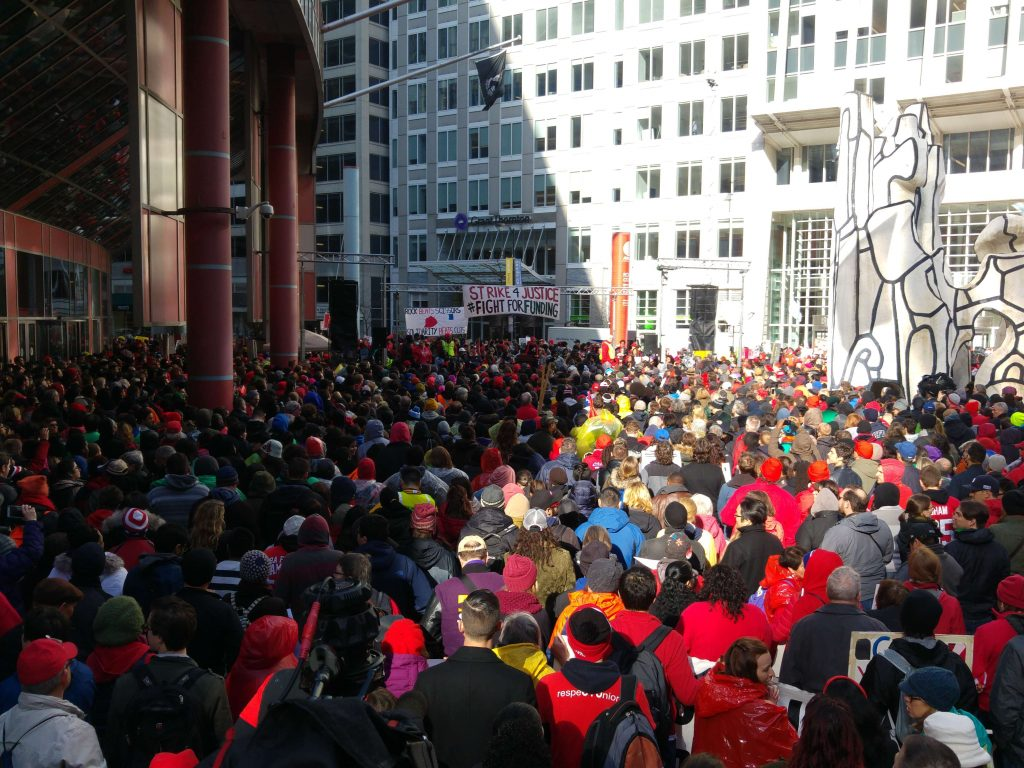 "Chicago teachers' rally 1 April 2016, banners read ""Strike 4 Justice, Fight For Funding"" and ""Rock Beats Scissors, Solidarity Beats Cuts"""