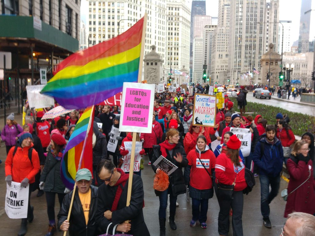 "Rainbow flags. Placards read ""LGBTQs for Education and Justice"", ""On Strike"" and ""Governor Rauner is the Wooorrst for Education"""