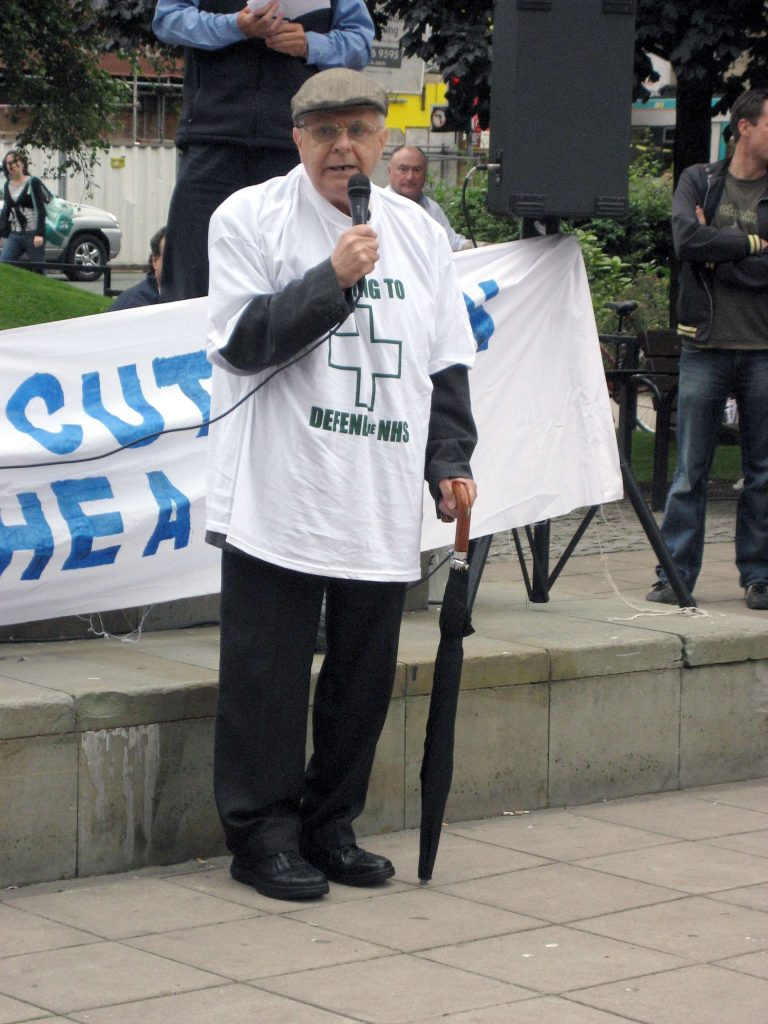 Bartley speaking into microphone wearing t-shirt for NHS